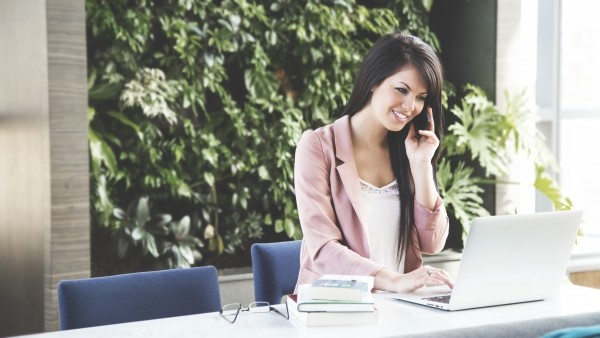 young-businesswoman-using-mobile-phone-and-laptop-in-office