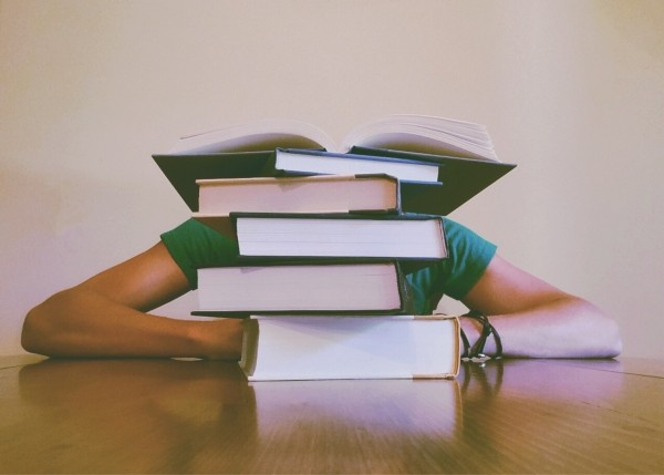 man-sitting-behind-pile-of-books